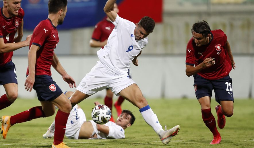 Cyprus' Dimitris Christofi, centre, controls the ball during an international friendly soccer match between Cyprus and Czech Republic at AEK arena in Larnaca, Cyprus, on Wednesday, Oct. 7, 2020. (AP Photo/Petros Karadjias)