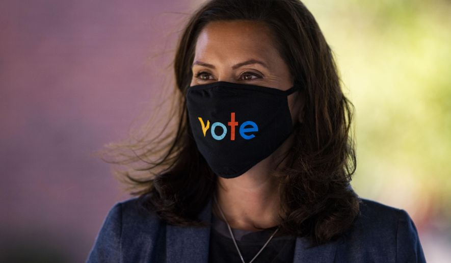 """Michigan Gov. Gretchen Whitmer wears a mask with the word """"vote"""" displayed on the front during a roundtable discussion on healthcare, Wednesday Oct. 7, 2020, in Kalamazoo, Mich. The arrest of a group of anti-government vigilantes in a kidnapping plot against Michigan Gov. Gretchen Whitmer presents a new twist in the 2020 political fight for the battleground state. (Nicole Hester/Ann Arbor News via AP)/"""