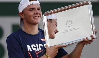Switzerland's Dominic Stephan Stricker holds the trophy after winning the junior men's final match of the French Open tennis tournament against Switzerland's Leandro Riedi at the Roland Garros stadium in Paris, France, Saturday, Oct. 10, 2020. (AP Photo/Alessandra Tarantino)
