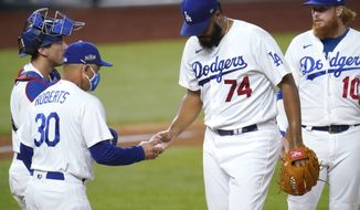 Los Angeles Dodgers manager Dave Roberts, left, takes Los Angeles Dodgers' Kenley Jansen (74) out of the game against the San Diego Padres during the ninth inning in Game 2 of a baseball National League Division Series Wednesday, Oct. 7, 2020, in Arlington, Texas. (AP Photo/Sue Ogrocki)