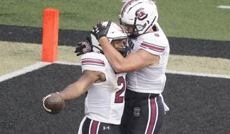 South Carolina running back Kevin Harris, left, is congratulated by tight end Nick Muse, right, after Harris scored a touchdown on a 25-yard run against Vanderbilt in the second half of an NCAA college football game Saturday, Oct. 10, 2020, in Nashville, Tenn. (AP Photo/Mark Humphrey)