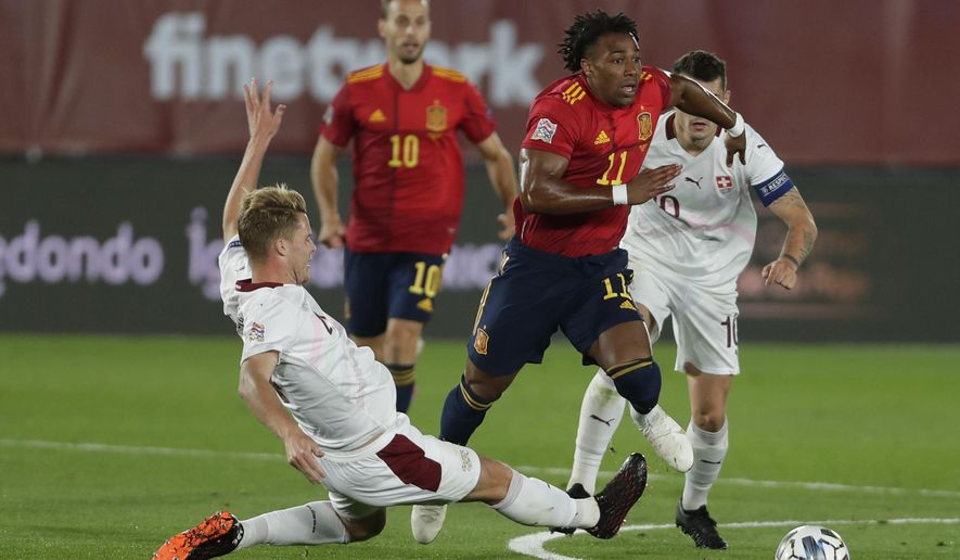 Switzerland's Renato Steffen, center, evedes a tackle by Switzerland's Nico Elvedi, left, during the UEFA Nations League soccer match between Spain and Switzerland in Madrid, Spain, Saturday, Oct. 10, 2020. (AP Photo/Manu Fernandez)