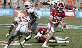 Oklahoma quarterback Tanner Mordecai (15) tries to get past Texas defensive back Chris Brown (15) during an NCAA college football game in Dallas, Saturday, Oct. 10, 2020. (AP Photo/Michael Ainsworth)
