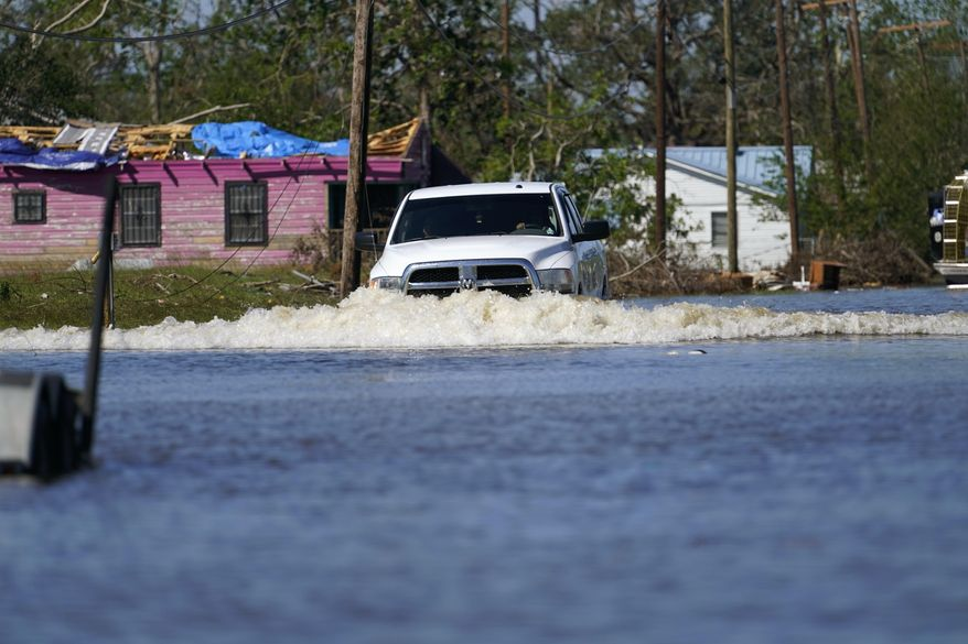 A truck drives through a flooded street in Lake Charles, La., Saturday, Oct. 10, 2020, past a home with damage from Hurricane Laura, after Hurricane Delta moved through on Friday. (AP Photo/Gerald Herbert)