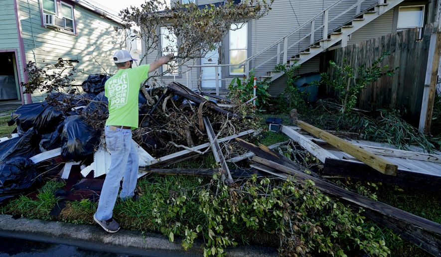 Caleb Cormier moves debris after Hurricane Delta moved through, Saturday, Oct. 10, 2020, in Lake Charles, La. Delta hit as a Category 2 hurricane with top winds of 100 mph (155 kph) before rapidly weakening over land. (AP Photo/Gerald Herbert)