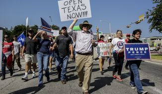 Jody Quimby and other protesters walk in protest against Gov. Greg Abbott's handling of the coronavirus pandemic near the governor's mansion in Austin on Saturday, Oct. 10, 2020. [Bronte Wittpenn /Austin American-Statesman via AP)