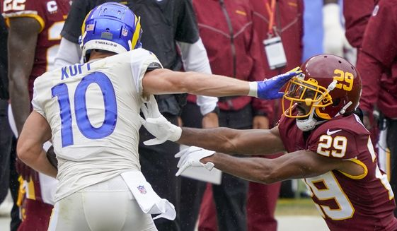 Los Angeles Rams' Cooper Kupp (10) tries to get away from Washington Football Team's Kendall Fuller (29) during the first half of an NFL football game Sunday, Oct. 11, 2020, in Landover, Md. (AP Photo/Susan Walsh)