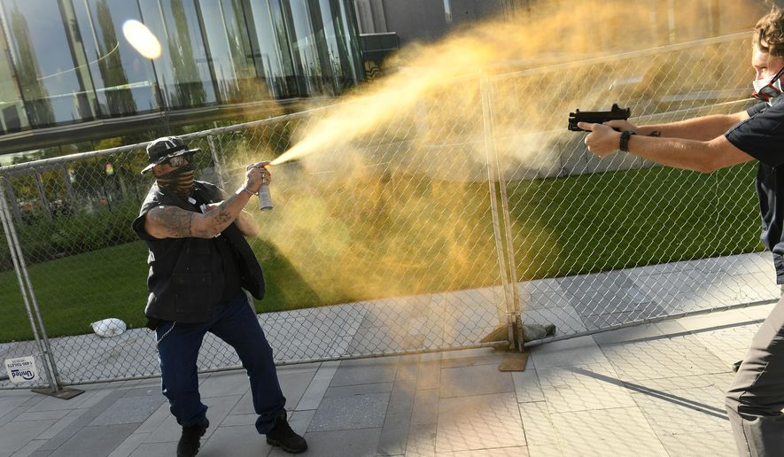 "A man sprays mace, left, as another man fatally fires a gun, Saturday, Oct. 10, 2020 in Denver. The man on the left side of the photo was supporting the ""Patriot Rally"" and sprayed mace at the man on the right side of the image. The man at right, then shot and killed the protester at left. A private security guard working for a TV station was in custody Saturday after a person died from a shooting that took place during dueling protests in downtown Denver, the Denver Post reported. (Helen H. Richardson/The Denver Post via AP)"
