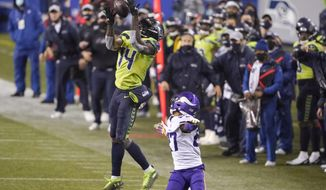 Seattle Seahawks' DK Metcalf (14) pulls in a long pass reception on the Seahawks' last series of an NFL football game as Minnesota Vikings' Cameron Dantzler defends late in the second half, Sunday, Oct. 11, 2020, in Seattle. The Seahawks won 27-26. (AP Photo/Ted S. Warren)