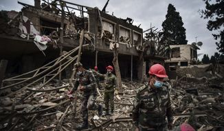 Azerbaijani soldiers and firefighters search for survivors after rocket fire overnight by Armenian forces, early Sunday, Oct. 11, 2020, in a residential area in Ganja, Azerbaijan's second largest city, near the border with Armenia. Several civilians were killed and dozens were wounded. Russian President Vladimir Putin brokered a cease-fire on Friday in a series of calls with President Ilham Aliyev of Azerbaijan and Armenia's Prime Minister Nikol Pashinian. (Ismail Coskun/IHA via AP)