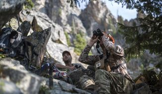 Jacob Glissmeyer, right, of Hoback, Wyo., searches for mountain goats high in the Teton Range in Grand Teton National Park, Wyo., in September, 2020. The National Park Service allowed qualified volunteers to help cull the non-native mountain goat population, which is threatening the survival of a dwindling population of bighorn sheep. (Ryan Dorgan/Jackson Hole News & Guide via AP)