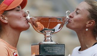 Hungary's Timea Babos,left, and France's Kristina Mladenovic hold the trophy after winning the women's doubles final match of the French Open tennis tournament against Chile's Alexa Guarachi and Desirae Krawczyk of the U.S. at the Roland Garros stadium in Paris, France, Sunday, Oct. 11, 2020. (AP Photo/Alessandra Tarantino)