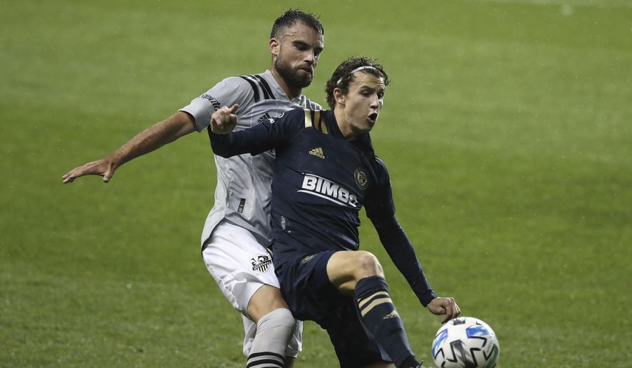 Brenden Aaronson, right, of the Philadelphia Union and Rudy Camacho of the Montreal Impact battle for the ball in the first half. The Philadelphia Union becomes the first Philadelphia-area team to allow fans in the stands for their game against Montreal on Sunday, Oct. 11, 2020, in Chester, Pa. (Charles Fox/The Philadelphia Inquirer via AP)