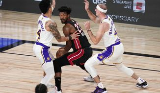 Miami Heat's Jimmy Butler (22) looks to pass against Los Angeles Lakers' Danny Green (14) and Alex Caruso (4) during the first half in Game 6 of basketball's NBA Finals Sunday, Oct. 11, 2020, in Lake Buena Vista, Fla. (AP Photo/John Raoux)