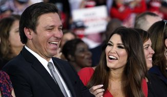 Florida Gov. Ron DeSantis and Kimberly Guilfoyle smile as President Donald Trump speaks during a campaign rally at Orlando Sanford International Airport, Monday, Oct. 12, 2020, in Sanford, Fla. (AP Photo/Evan Vucci)
