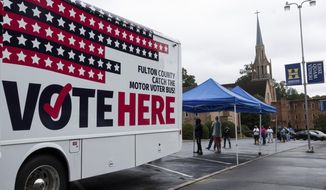 In this file photo, one of Fulton County's two mobile voting stations sits in the parking lot of Morningside Baptist Church on Monday morning, Oct. 12, 2020, for the first day of early voting. (Ben Gray/Atlanta Journal-Constitution via AP)