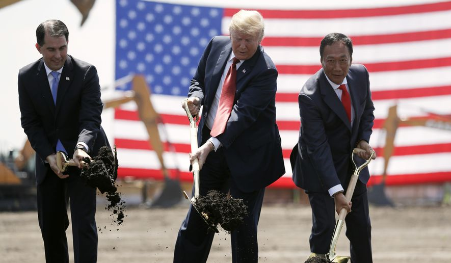In this June 28, 2018, file photo, President Donald Trump, center, along with Wisconsin Gov. Scott Walker, left, and then, Foxconn Chairman Terry Gou, participate in a groundbreaking event for the new Foxconn facility in Mt. Pleasant, Wis. Wisconsin told Foxconn on Monday, Oct. 12, 2020, that it won't qualify for billions of dollars in state tax credits unless it strikes a new deal for the now, scaled-back factory complex that was originally negotiated in 2017. (AP Photo/Evan Vucci, File)