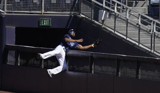 Tampa Bay Rays right fielder Manuel Margot reaches over a right field wall after catching a foul ball by Houston Astros center fielder George Springer during the second inning in Game 2 of a baseball American League Championship Series, Monday, Oct. 12, 2020, in San Diego.(AP Photo/Gregory Bull)