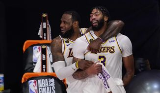 Los Angeles Lakers' LeBron James (23) and Anthony Davis (3) celebrate after the Lakers defeated the Miami Heat 106-93 in Game 6 of basketball's NBA Finals Sunday, Oct. 11, 2020, in Lake Buena Vista, Fla. (AP Photo/Mark J. Terrill)