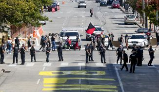 Tulsa Police block off a street where protestors painted a new Black Lives Matter mural in front of Tulsa City Hall while protestors leave during a protest on Saturday, Oct. 10, 2020. The protest was in response to the repaving of a street that had a Black Lives Matter mural painted on it in Greenwood, Okla. (Ian Maule/Tulsa World via AP)