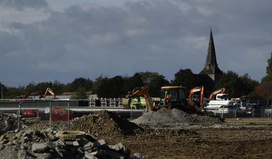 Construction takes place backdropped by the spire of St Mary's Church, of which parts date back to the 12th century, on a post-Brexit customs clearance border post facility on land that was previously a field between the villages of Mersham and Sevington in the county of Kent, south east England, Tuesday, Oct. 6, 2020. In the corner of Britain known as the Garden of England, Brexit is literally taking concrete form. Diggers, dump trucks and cement mixers are transforming a field in the village of Sevington into a customs clearance depot with room for up to 2,000 trucks. It's part of Britain's new border with the European Union, and no one asked the locals for their permission. (AP Photo/Matt Dunham)