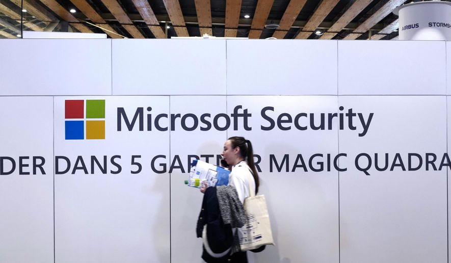 A woman walks in front of the Microsoft stand during the Cybersecurity Conference in Lille, northern France, Wednesday, Jan. 29, 2020. Microsoft announced legal action Monday, Oct. 12, 2020, seeking to disrupt a major cybercrime digital network that uses more than 1 million zombie computers to loot bank accounts and spread ransomware, which experts consider a major threat to the U.S. presidential election. (AP Photo/Michel Spingler)