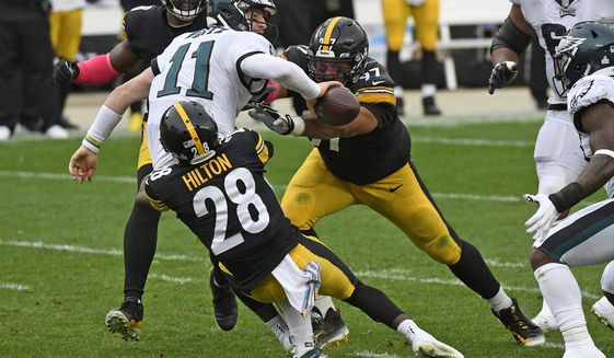 Philadelphia Eagles quarterback Carson Wentz (11) is sacked by Pittsburgh Steelers cornerback Mike Hilton (28) and Cameron Heyward (97) during the second half of an NFL football game in Pittsburgh, Sunday, Oct. 11, 2020. (AP Photo/Don Wright)