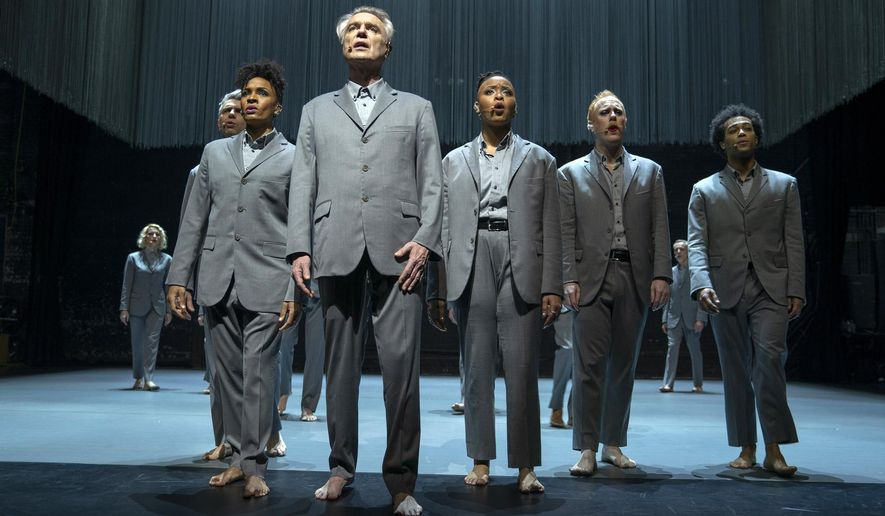 """This image released by HBO shows David Byrne, foreground, in a scene from """"David Byrne's American Utopia."""" (HBO via AP)"""