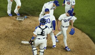 Los Angeles Dodgers starting pitcher Walker Buehler is taken out of the game by manager Dave Roberts during the sixth inning in Game 1 of a baseball National League Championship Series against the Atlanta Braves Monday, Oct. 12, 2020, in Arlington, Texas. (AP Photo/David J. Phillip)