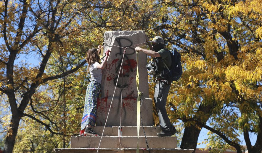 """Demonstrators secure a rope around the centerpiece of a solid stone obelisk before tearing it down on Monday, Oct. 12, 2020, in Santa Fe, New Mexico. In July, activists called for the monument to be removed during peaceful protests. On Monday, a group of around 50 protesters pulled down segments of the memorial, which commemorates federal soldiers who fought against Indigenous people in the 19th Century. A reference to """"savage"""" Indians was chiseled from the monument decades ago. (AP Photo/Cedar Attanasio)"""