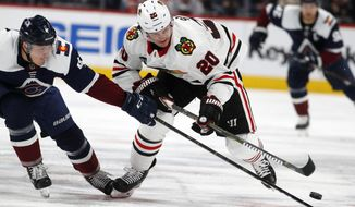 FILE - In this Dec. 21, 2018, file photo, Colorado Avalanche defenseman Tyson Barrie, left, knocks the puck away from Chicago Blackhawks left wing Brandon Saad during the second period of an NHL hockey game in Denver. Saad is part of the new-look Avalanche squad after being acquired in a trade from Chicago. (AP Photo/David Zalubowski, File)
