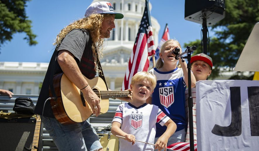 Sean Feucht sings on stage with his family, Ezra, 5, Keturah, 9, and Malachi, 7, in front of the west steps of the state Capitol as protesters gathered at Liberty Fest to protest Gov. Gavin Newsom's stay-at-home order in Sacramento, Calif., Saturday, May 23, 2020. Hundreds of protesters rallied outside the Capitol on Saturday to protest against California's stay-at-home orders even as residents entered the Memorial Day weekend with newly expanded options for going to the beach, barbecuing and shopping. (Jason Pierce/The Sacramento Bee via AP)