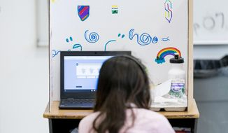 In this Friday, Sept. 18, 2020, photo a student works in class at Meridien Public Charter School, in Washington. Several DC charter schools have been doing in-person teaching for small groups of students. (AP Photo/Andrew Harnik)  **FILE**