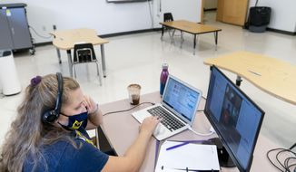 In this Friday, Sept. 18, 2020, photo fifth grade teacher Lauren Furst leads an online class at Meridien Public Charter School, in Washington. Several D.C. charter schools have been doing in-person teaching for small groups of students. (AP Photo/Andrew Harnik)  **FILE**