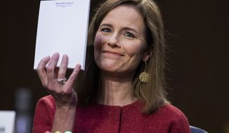 Supreme Court nominee Amy Coney Barrett holds up her notepad as she speaks during her confirmation hearing before the Senate Judiciary Committee on Capitol Hill in Washington, Tuesday, Oct. 13, 2020. (Tom Williams/Pool via AP)