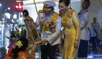 Thai people give a picture of Buddha to Thailand's King Maha Vajiralongkorn and Queen Suthida, as leave the Grand Palace after ceremony marking the fourth anniversary of the death of late Thai King Bhumibol Adulyadej, Bangkok, Thailand, Tuesday, Oct. 13, 2020. (AP Photo/Wason Wanichakorn)