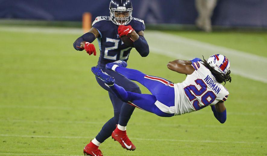 Tennessee Titans running back Derrick Henry (22) knocks down Buffalo Bills cornerback Josh Norman (29) in the first half of an NFL football game Tuesday, Oct. 13, 2020, in Nashville, Tenn. (AP Photo/Wade Payne)
