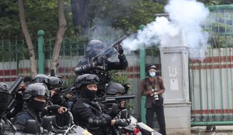 A police officer fires his tear gas launcher during a protest against the new Job Creation Law approved by Parliament last week in Jakarta, Indonesia, Tuesday, Oct. 13, 2020. Thousands of conservative Muslims marched in Indonesia's capital on Tuesday demanding that the government revoke the law they say will cripple labor rights. (AP Photo/Tatan Syuflana)