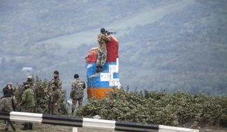 A sniper of Nagorno-Karabakh's militia observes the land ahead during a military conflict near Hadrut, the separatist region of Nagorno-Karabakh, Sunday, Oct. 11, 2020. Armenia and Azerbaijan on Monday accused each other of attacks over the separatist territory of Nagorno-Karabakh despite a cease-fire deal brokered by Russia to try to end the worst outbreak of hostilities in the region in decades. (AP Photo)