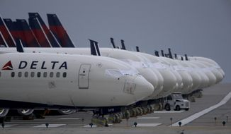 FILE - In this May 14, 2020 file photo, several dozen mothballed Delta Air Lines jets are parked on a closed runway at Kansas City International Airport  in Kansas City, Mo. Delta Air Lines is the first carrier to report financial results for the third quarter, and the numbers are grim. Delta said Tuesday, Oct. 13 that it lost nearly $6.9 billion as travel remain depressed over the normally peak vacation season because of the pandemic.  (AP Photo/Charlie Riedel, File)