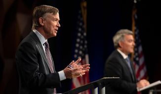 Democratic challenger John Hickenlooper, front, talks during a debate with Republican U.S. Senator Cory Gardner during a debate between the candidates Tuesday, Oct. 13, 2020, in Fort Collins, Colo. (Pool Photo By Bethany Baker/Fort Collins Coloradoan via AP) ** FILE **