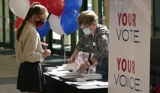 During a break between morning church services, Beverly Sides, right, with the Prestonwood Cultural Impact Team shows Suzie Brewer election voter guides for various north Texas counties at Prestonwood Baptist Church Sunday, Oct. 11, 2020, in Plano, Texas. Evangelical churches and their suburban members are a key to President Trump's voter support in Texas. (AP Photo/LM Otero)
