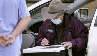 With an election official looking on an elderly voter uses the drive-thru option to vote outside Richardson City Hall during early voting Tuesday, Oct. 13, 2020, in Richardson, Texas. (AP Photo/LM Otero)