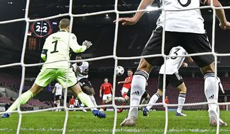 Switzerland's Mario Gavranovic, center, scores his side's third goal against Germany's goalkeeper Manuel Neuer during the UEFA Nations League soccer match between Germany and Switzerland in Cologne, Germany, Tuesday, Oct. 13, 2020. (AP Photo/Martin Meissner)