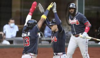 Atlanta Braves first baseman Freddie Freeman, right, celebrates his two-run home run with teammate Ronald Acuna (13) against the Los Angeles Dodgers during the fourth inning in Game 2 Tuesday, Oct. 13, 2020,  in the best-of-seven National League Championship Series at Globe Life Field in Arlington, Texas. (Curtis Compton/Atlanta Journal-Constitution via AP)  **FiLE**