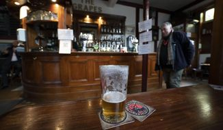 A view of a beer glass, at the Dispensary pub in Liverpool, England, Monday Oct 12, 2020. The British government has carved England into three tiers of risk in a bid to slow the spread of a resurgent coronavirus. The northern city of Liverpool is in the highest category and will close pubs, gyms and betting shops. (AP Photo/Jon Super)