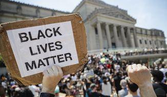 """In this June 19, 2020, file photo, a protester holds a sign that reads """"BLACK LIVES MATTER"""" during a Juneteenth rally outside the Brooklyn Museum in the Brooklyn borough of New York. Juneteenth commemorates when the last enslaved African Americans learned they were free 155 years ago. New York Gov. Andrew Cuomo signed legislation Wednesday, Oct. 14, 2020, officially making Juneteenth a New York state holiday. Although President Abraham Lincoln issued the Emancipation Proclamation on Jan. 1, 1863, it wasn't until June 19th, 1865, that enslaved people in Galveston, Texas, found out about it from Union army personnel, making them among the last to know about their freedom. (AP Photo/John Minchillo, File)"""
