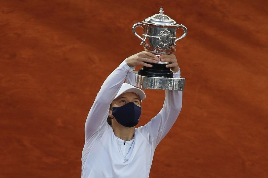 Poland's Iga Swiatek lifts the trophy after winning the final match of the French Open tennis tournament against Sofia Kenin of the U.S. in two sets 6-4, 6-1, at the Roland Garros stadium in Paris, France, Saturday, Oct. 10, 2020. (AP Photo/Alessandra Tarantino)
