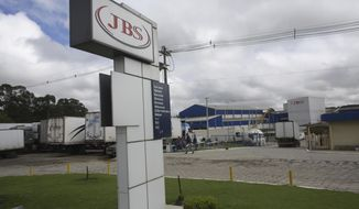 FILE - In this March 21, 2017 file photo, a multilingual sign welcomes visitors at the meatpacking company JBS in Lapa, Parana state, Brazil. An owner of the world's largest meatpacker pleaded guilty in U.S. federal court on Wednesday, Oct. 14, 2020, to paying nearly $150 million in bribes for over a decade to high-level government officials in Brazil. (AP Photo/Eraldo Peres, File)