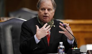 FILE - In this Thursday, May 7, 2020, file photo, U.S. Sen. Doug Jones, D-Ala., speaks at Capitol Hill in Washington. Tommy Tuberville's quest for a seat in the U.S. Senate is powered by the reputation he gained as Auburn University's football coach. But in the years since, the Republican has been mired in business failings, a lawsuit and even a questionable charity that raises money but gives very little away. In trying to raise doubts Tuberville's fitness for office, Jones has pointed to Tuberville's involvement in a failed hedge fund. (AP Photo/Andrew Harnik, Pool, File)